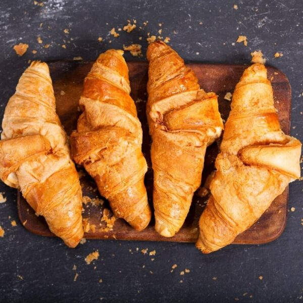 four butter croissants on wooden cutting board a