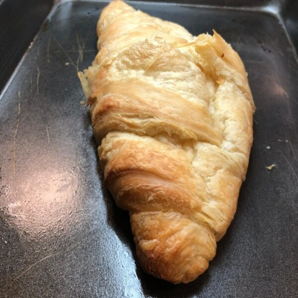 one butter croissant on a baking tray