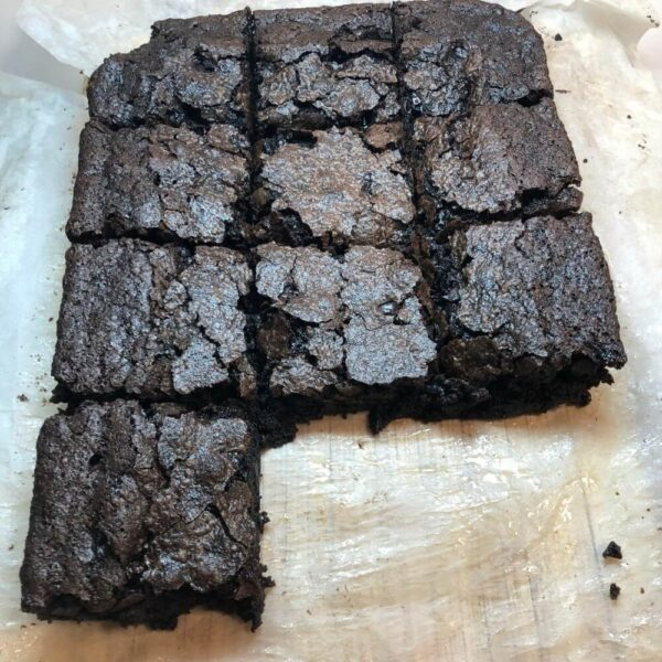 a batch of brownies on a baking tray containing baking paper