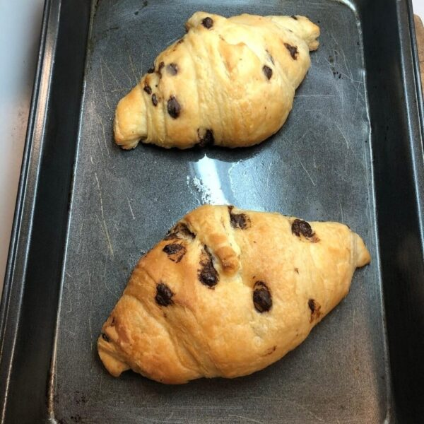 2 chocolate croissants on a baking tray